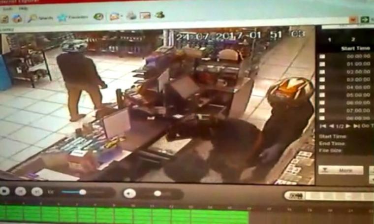 Perampok saat menjalankan aksinya yang terekam CCTV di salah satu minimarket di Kota Serang. (Foto: TitikNOL)