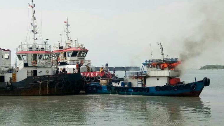 Kapal TB Satria Mandiri yang terbakar di Peiraran Bojonegara terlihat dilakukan proses pemadaman.(Foto: Ist).