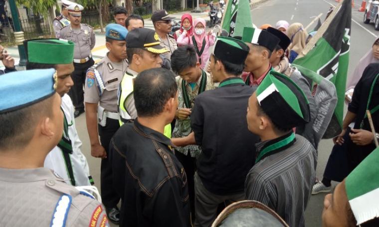 Kapolsek Pulomerak, Kompol Kamarul Wahyudi saat menenangkan mahasiswa pengunjuk rasa yang tidak terima rekannya dipukuli. (Foto: TitikNOL)