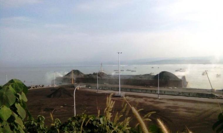 Kepulan asap terlihat di kapal tongkang pengangkut batu bara yang bersandar di dermaga milik PT Cemindo Gemilang. (Foto: TitikNOL)