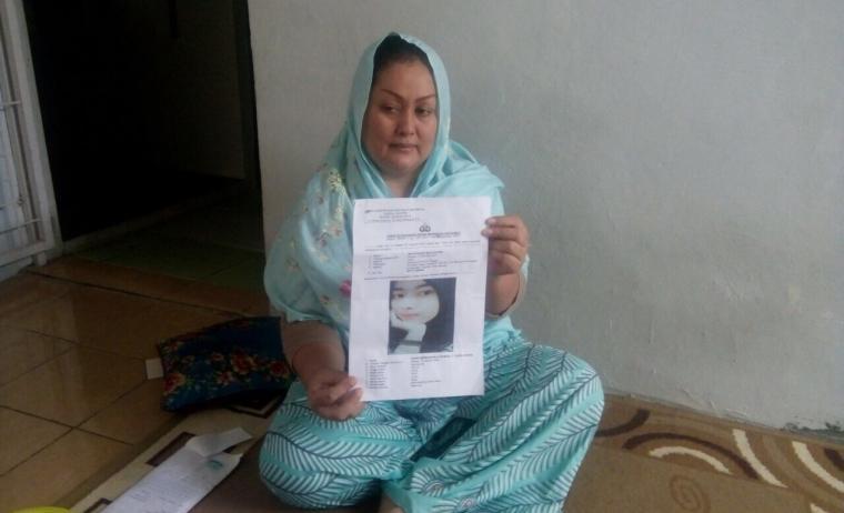 Ibu Machfudoh menunjukan gambar anaknya yang hilang pada surat laporan kehilangan. (Foto: TitikNOL)