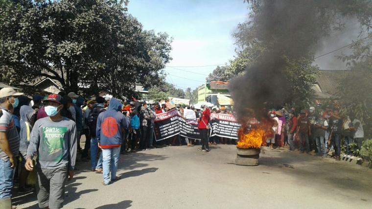 Ratusan warga yang tergabung di Aliansi Masyarakat Cilangkahan (AMC), menggelar aksi unjuk rasa di ruas jalan Malingping - Bayah. (Foto: TitikNOL)