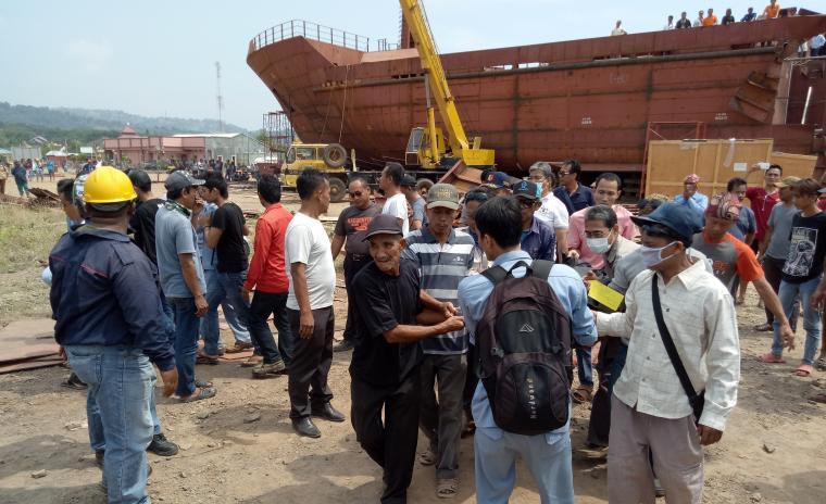 Petugas kepolisian dan warga saat melakukan evakuasi korban meninggal di galangan kapal milik PT Krakatau Shipyard Puloampel. (Foto: TitikNOL)