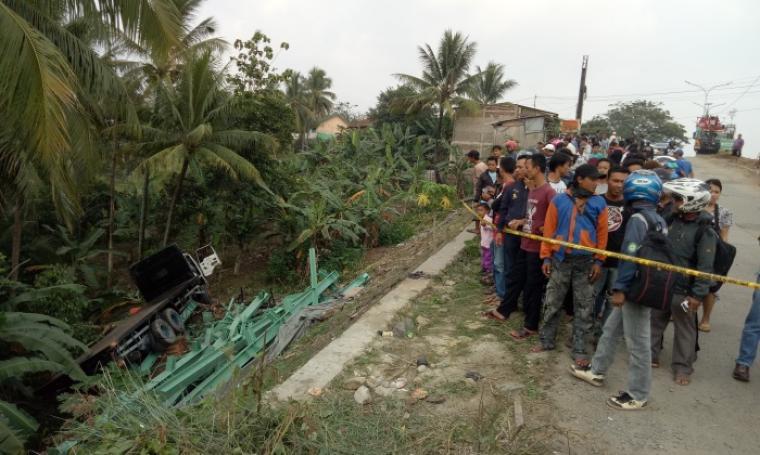 Sejumlah warga menyaksikan truk tronton yang masuk ke jurang di Jalan Lingkar Selatan. (Foto: TitikNOL)