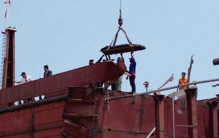 Petugas saat melakukan evakuasi salah satu korban tewas dari dalam kapal yang meledak. (Foto: TitikNOL)