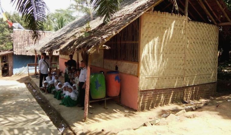 Puluhan siswa MI mengikuti kegiatan KBM di gubuk yang sudah rapuh dan bocor. (Dok: TitikNOL)