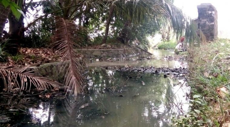 Seorang warga sedang melakukan aktivitas di saluran irigasi yang kotor. (Foto: TitikNOL)