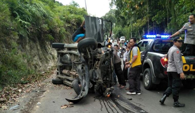 Polisi dibantu warga tengah berupaya mengevakuasi mobil avanza yang terbalik dan ringsek di Ruas Jalan Bojongmanik - Leuwidamar. (Foto: Ist)