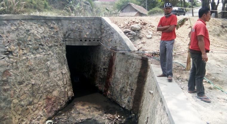 Warga tengah memeriksa saluran air yang mengandung limbah oli yang diduga berasal dari perusahaan PT Cemindo Gemilang. (Foto: TitikNOL)