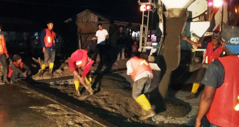 Sejumlah pekerja tengah melakukan membetonan jalan di ruas jalan yang menghubungkan antar dua Kampung. (Foto: TitikNOL)