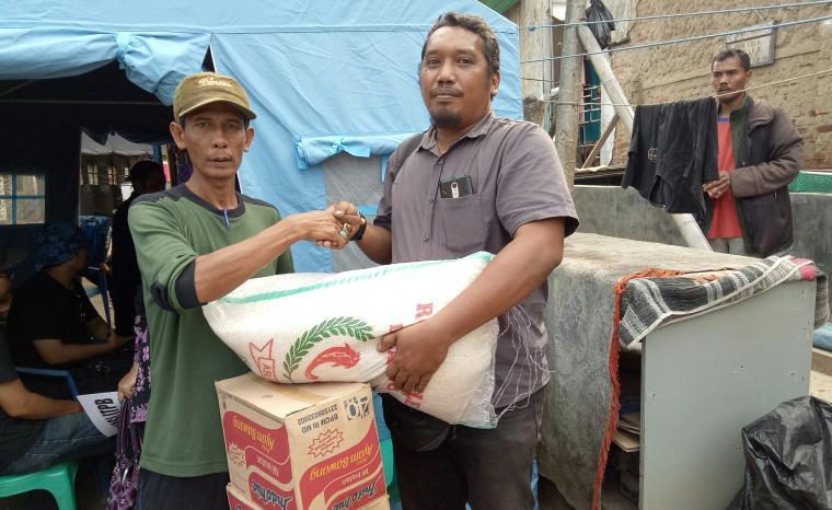 Ketua PWHC, Ronald Ricardo Siagian, saat menyerahkan bantuan ke posko korban kebakaran di Lingkungan Tegal Cabe, Keluruhan Citangkil. (Foto: TitikNOL)