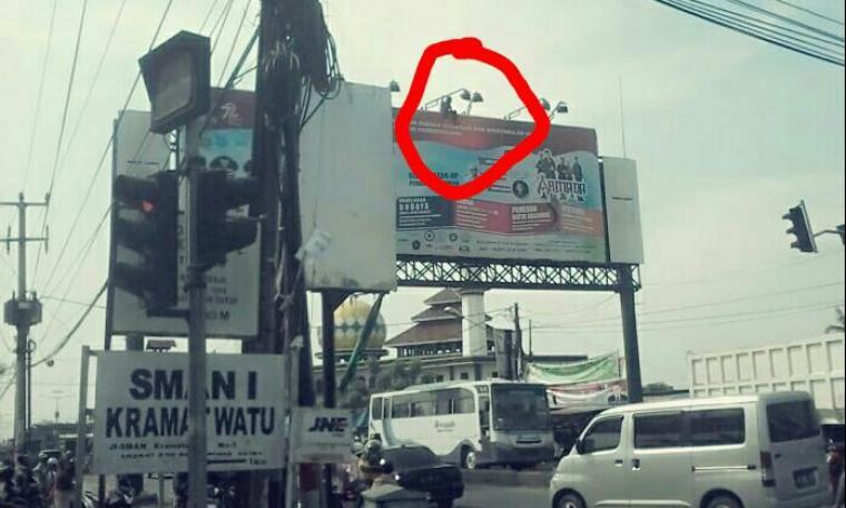 Hasta, saat memanjat papan reklame (bilboard) yang ada di jalan Serang - Cilegon. (Foto: Ist)