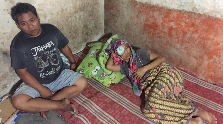 Nurhayati penderita tumor ganas tertidur lemah diatas kasur ditemani suaminya, Zaenal Arifin. (Foto: TitikNOL)