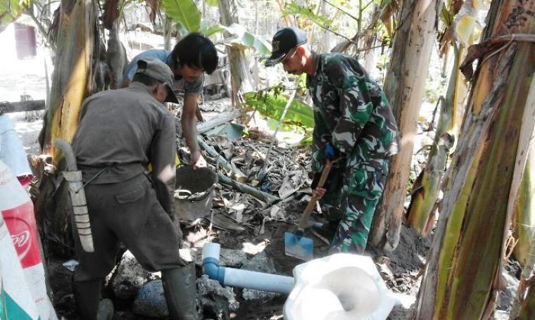 Salah seorang anggota TNI dibantu warga membangun jamban. (Foto: Ist)