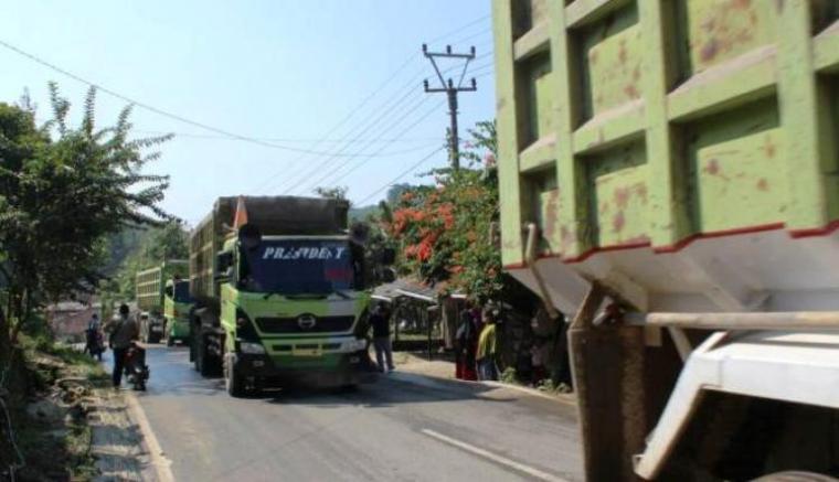 Iring-iringan kendaraan berat yang mengangkut material milik PT Cemindo Gemilang, saat melintas di jalan nasional di Desa Pamubulan. (Foto: Ist)