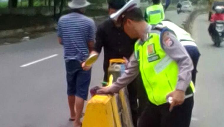 Petugas gabungan Polsek Cikande dan Satuan Lalulintas Polres Serang melakukan pengecetan beton pemisah jalan di ruas jalan raya Serang - Jakarta. (Foto: TitikNOL)