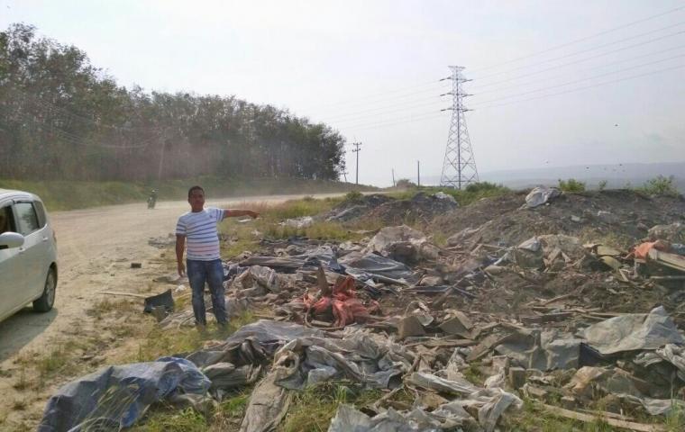 Seorang pengguna jalan menunjukan tumpukan limbah sampah yang berserakan di pinggir jalan nasional Bayah - Cibareno. (Foto: TitikNOL)