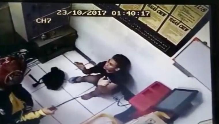 Perampok terekam CCTV tengah mengancam pegawai minimarket menggunakan senjata tajam. (Foto: Ist)