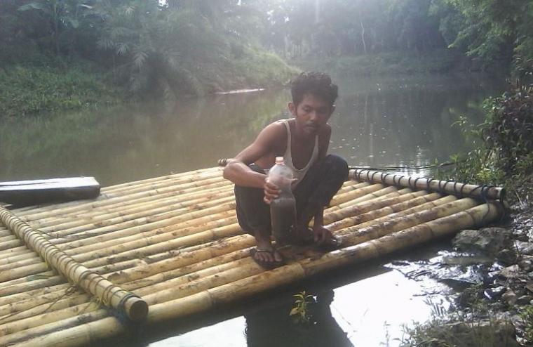 Salah seorang warga Tamansari, pengguna air Sungai Ciliman saat menunjukan air Sungai yang tercemar limbah CPO. (Foto: Ist)