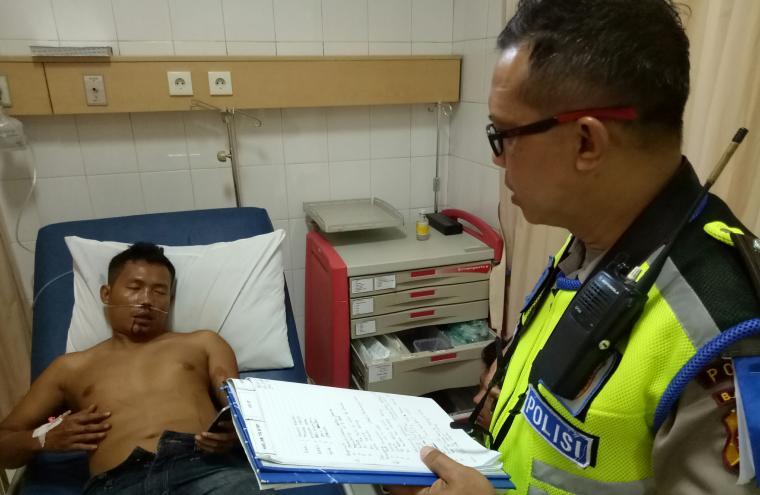 Petugas laka lantas Polda Banten Aiptu Andre, saat memeriksa Dawiri, korban luka berat kecelakaan di tol Merak - Tangerang. (Foto: Ist)