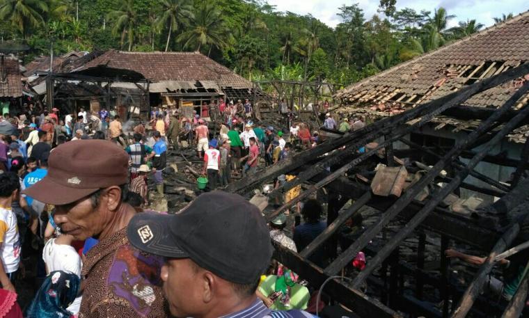 Sejumlah warga berada di puing rumah yang terbakar. (Foto: Ist)