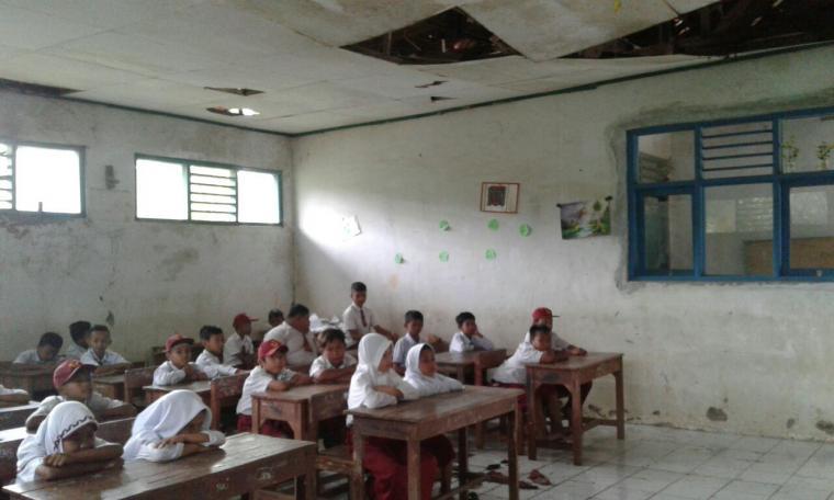 Sejumlah siswa saat belajar di sebuah ruang kelas yang penyangga genting dan plafonya lapuk dan terancam roboh. (Foto: TitikNOL)