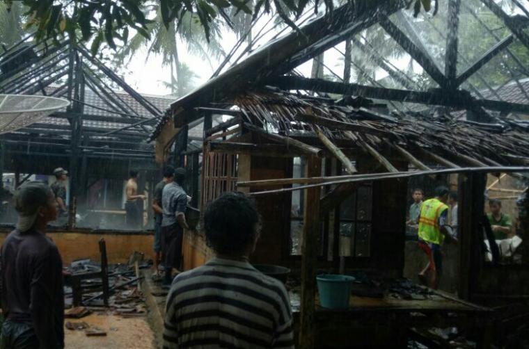 Sejumlah warga menyaksikan rumah yang hangus terbakar. (Foto: TitikNOL)
