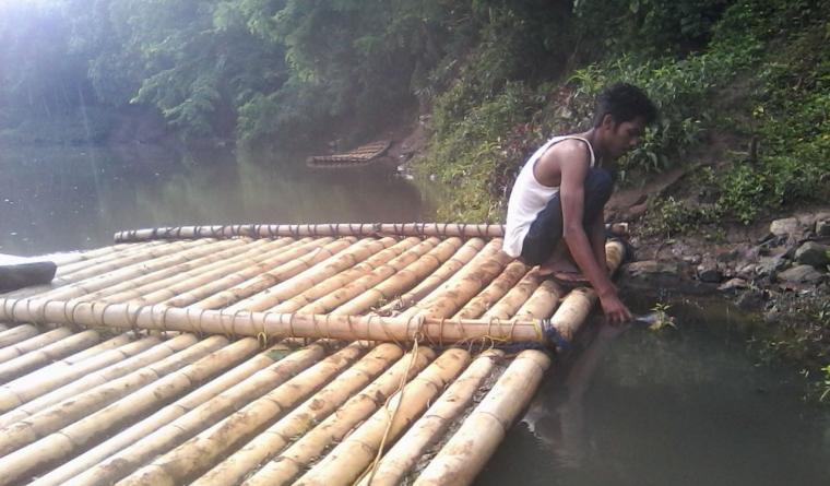 Salah seorang warga, saat menunjukan air Sungai Ciliman berwarna hitam pekat. (Foto: TitikNOL)