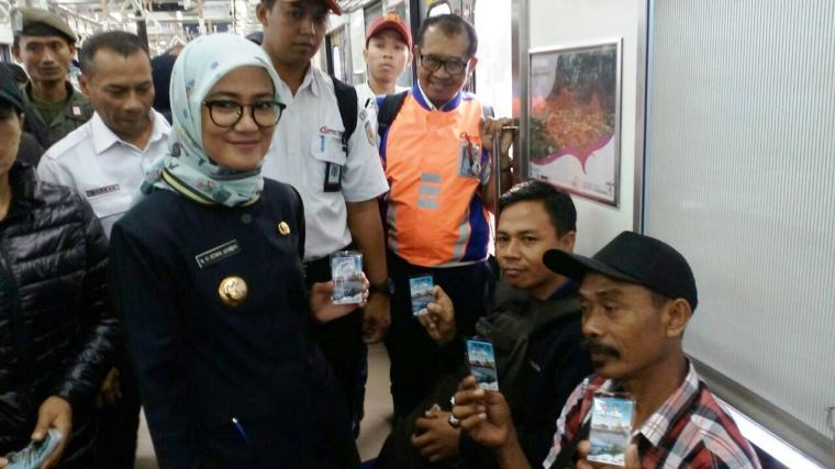 Bupati Lebak Iti Octavia Jayabaya saat membagikan Kartu Multi Trip (KMT) Commuter Line secara gratis kepada sejumlah penumpang. (Foto: TitikNOL)