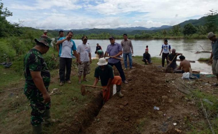Anggota Koramil 0315 Bayah Bersama Warga saat Membetulkan Bantaran Sungai yang Abrasi. (Foto: TitikNOL)