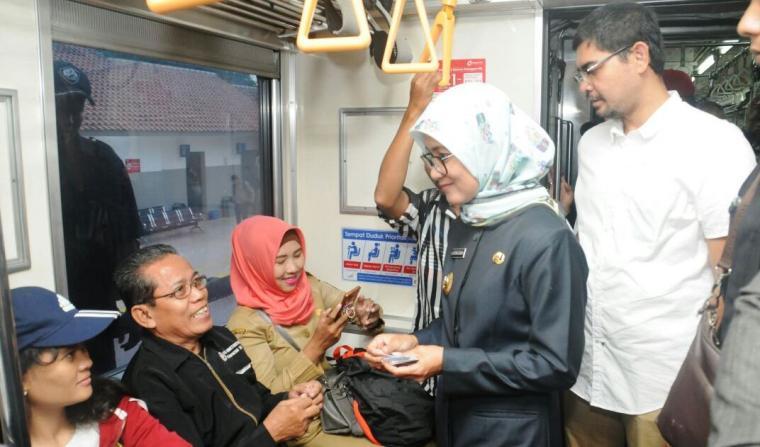 Bupati Lebak Iti Octavia Jayabaya didampingi suami (M. Farid Darmawan) saat tengah membagikan KMT gratis kepada penumpang Kereta di Stasiun Rangkasbitung, hari ini. (Foto: TitikNOL)