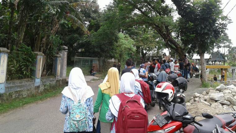 Puluhan warga menyaksikan lokasi penggerebekan gudang tempat memproduksi obat terlarang jenis Zenith Carnophen di Kampung Ciodeng, Desa Jatimulya, Kecamatan Rangkasbitung. (Foto: TitikNOL)