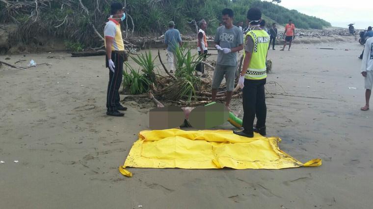 Petugas tim SAR saat mengevakuasi jasad Erik ke pantai. (Foto: Ist)