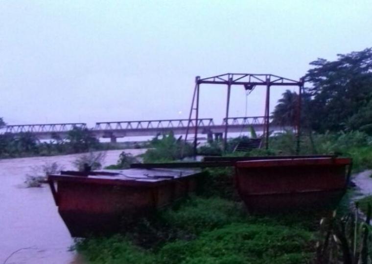 Bangkai kapal Tongkang yang tersandar dibibir sungai Cimadur, Desa Bayah Barat, Kecamatan Bayah membahayakan terhadap ratusan perahu nelayan. (Foto: TitikNOL)