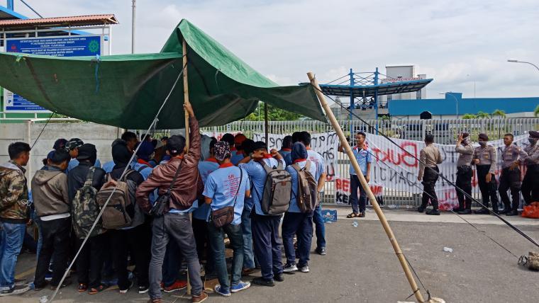 Suasana aksi unjuk rasa di pintu gerbang PT Nutrindo Bogarasa yang berada di Kelurahan Tegal Ratu, Kecamatan Ciwandan, Kota Cilegon. (Foto: TitikNOL)