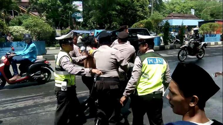Anggota polisi saat mengamankan mahasiswa dalam aksi peristiwa Malari yang berakhir ricuh. (Foto: TitikNOL)