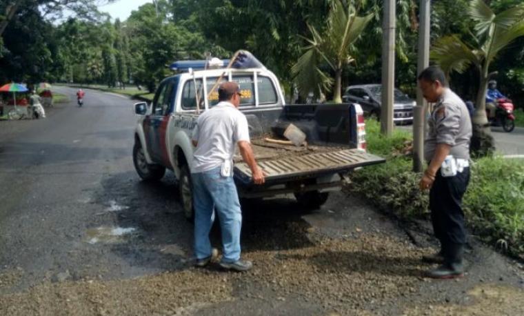 Petugas Satlantas Polres Cilegon saat menambal jalan rusak. (Foto: Ist).