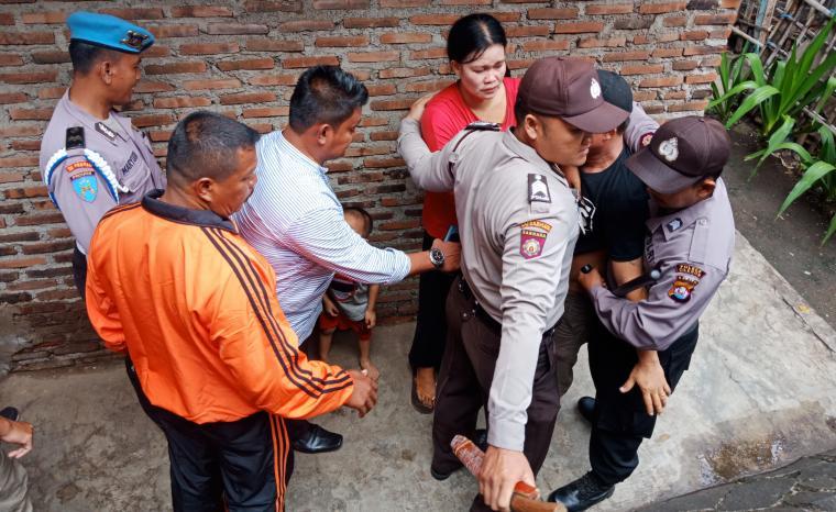 Petugas kepolisian saat mengamankan pemilik warung remang-remang yang berusaha menghalangi petugas. (Foto: TitikNOL)