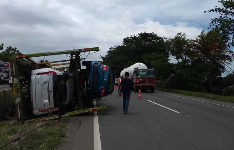 Truk bernomor polisi B 9922 AD yang mengangkut kendaraan mobil mewah Terguling di Tol Tangerang - Merak. (Foto: TitikNOL).