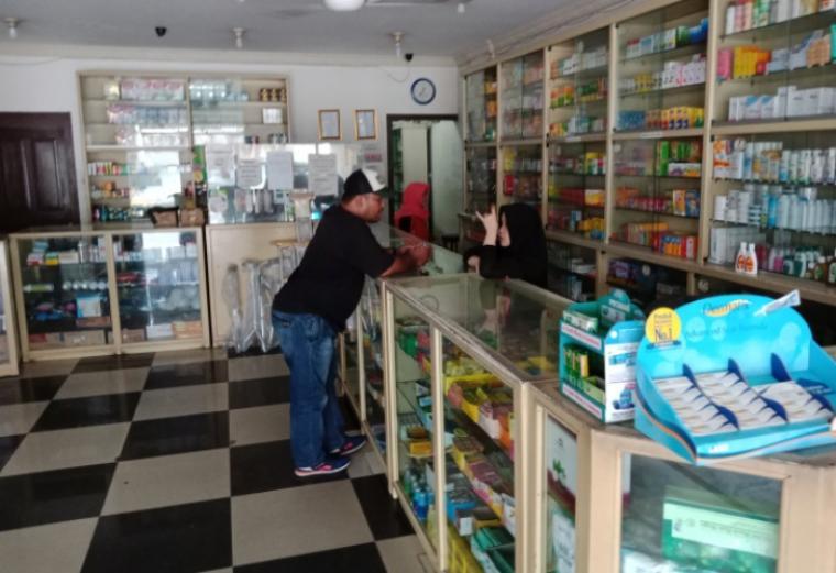 Karyawan apotek Gama saat melayani salah seorang warga yang membeli obat Albothyl. (Foto: TitikNOL)