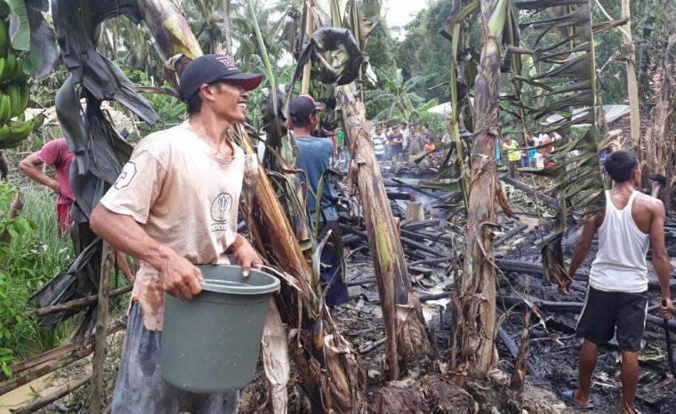 Warga di Kampung Sirnasari, Desa Karang Kamulyan, Kecamatan Cihara, sedang memadamkan api dengan ember. (Foto: Ist)