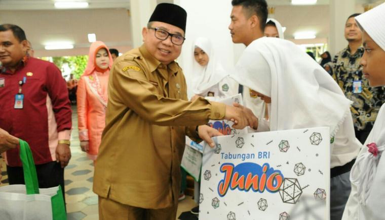 Pjs Bupati Lebak Ino S Rawita saat menyerahkan secara simbolis bantuan PKH dan Rastra. (Foto: TitikNOL)