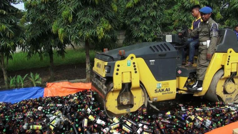 Petugas satpol PP Kota Serang saat musnahkan minuman keras berbagai merk. (Foto: TitikNOL)