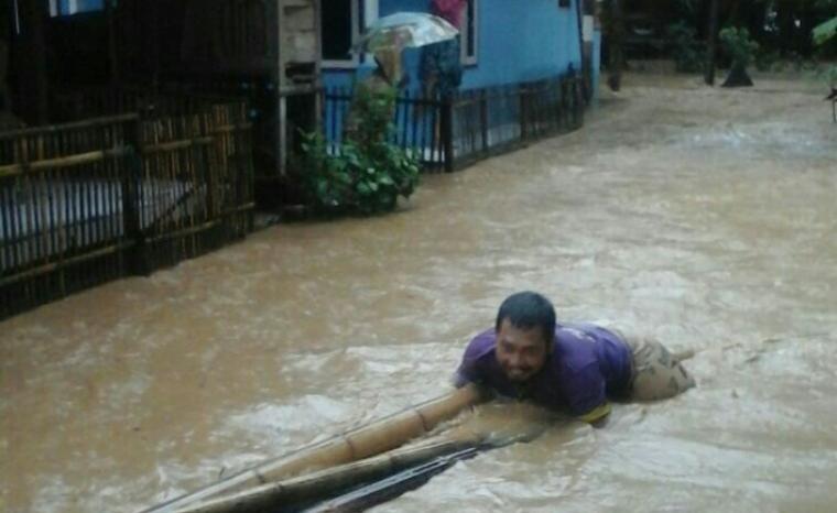 Seorang warga membawa kayu dan bambu di depan rumah yang terendam banjir. (Foto: Ist)