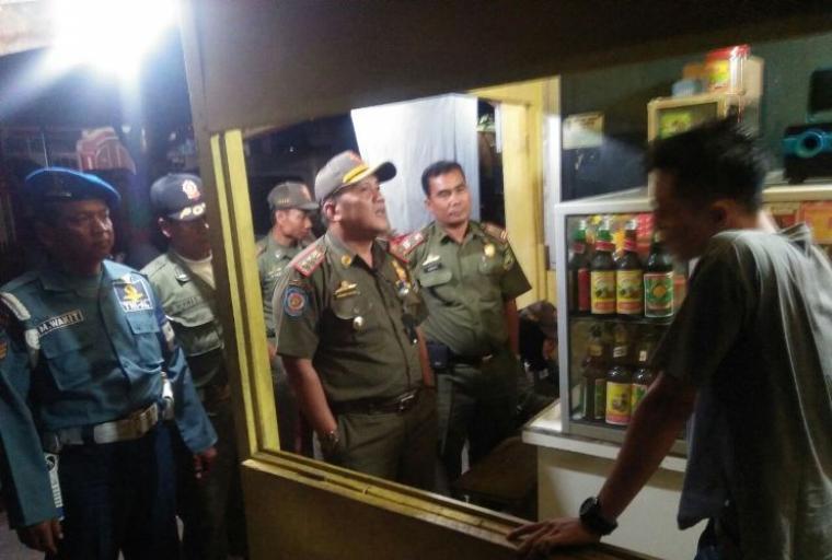 Petugas gabungan saat merazia minuman keras di warung jamu. (Foto: TitikNOL)