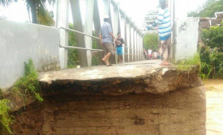 Sejumlah warga melihat jembatan yang terputus. (Foto: TitikNOL)