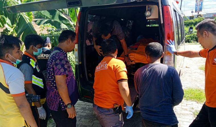 Petugas kepolisian saat mengevakuasi korban tertabrak kereta ke mobil ambulance. (Foto: TitikNOL)