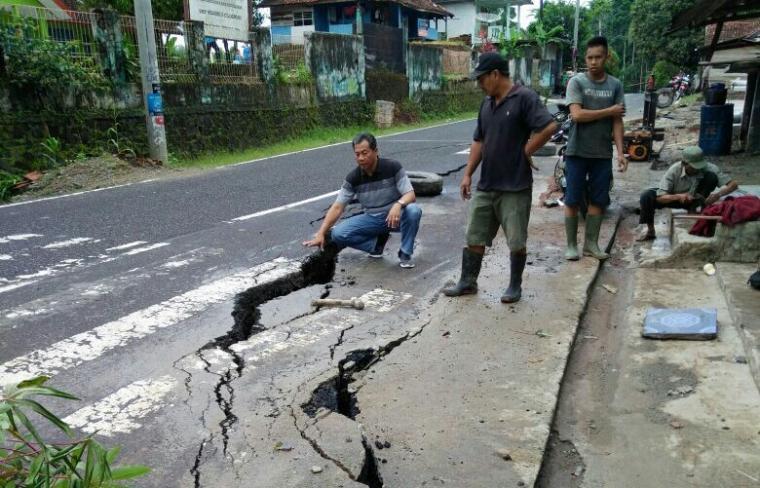 Sejumlah warga menunjukan Ruas Jalan Nasional Bayah - Cibareno yang Amblas. (Foto: TitikNOL)