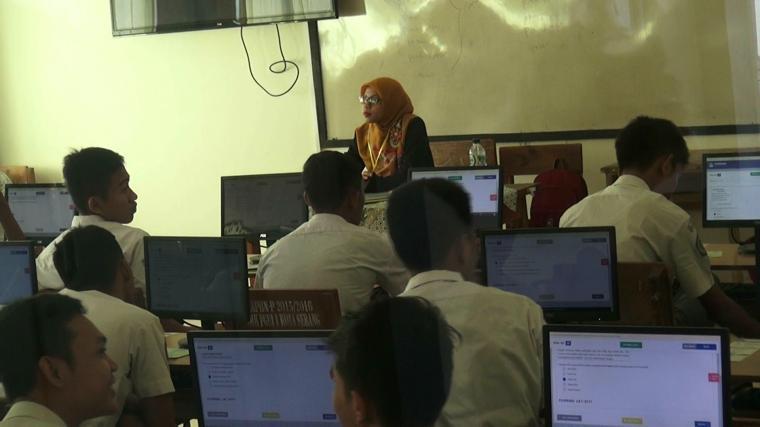 Seorang guru sedang mengawasi para siswa yang sedang ujian nasional. (Foto: TitikNOL)