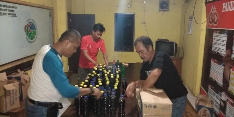 Petugas polisi sedang menyusun barang bukti minuman keras botol dan oplosan yang diamankan dari rumah DS. (Foto: TitikNOL)